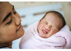 母亲看着躺在母亲手中的婴儿_5897175