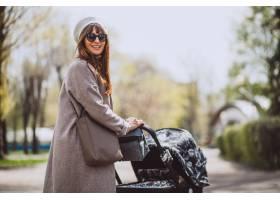 年轻的母亲坐在公园里的婴儿车里_4758582