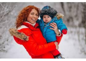 母亲和她的小儿子一起在冬季公园里_3656035