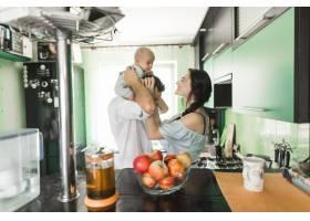 母亲在厨房里抱着坐在男人肩上的婴儿玩耍_3293427