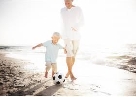 父子俩在海边踢足球_2862252