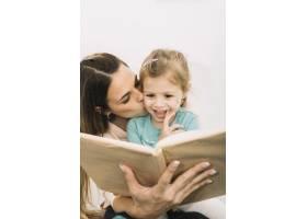 母亲边看书边亲吻女儿_2857130