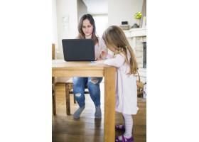 女孩在妈妈面前用笔记本电脑学习_2602098
