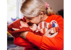 穿着红色毛衣的母亲怀里抱着刚出生的小婴儿_1617092