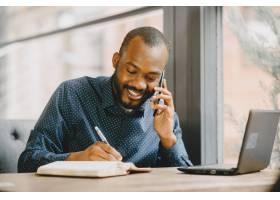 工作在膝上型计算机后和谈话在电话后的非裔_15318794