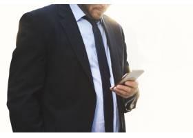 凝视在白色背景的智能手机的商人_15601209