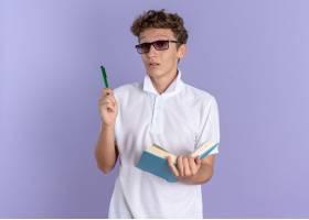 拿着书和笔的白色polo衬衣佩带的玻璃的学生_17071814