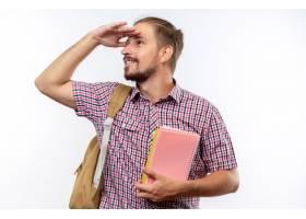 拿着书的微笑的年轻人学生佩带的背包看距离_17545047