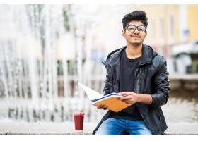 拿着堆书的印地安学生人坐在街道的喷泉附近_9077359