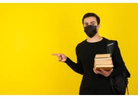 拿着学院书和指向的医疗面具的年轻男学生画_17289441