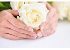 女性手部美手美甲与黄色玫瑰花