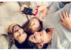 躺着头靠在一起的家庭成员