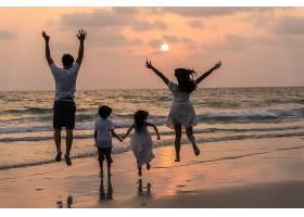 落日海边跳跃欢呼的家庭