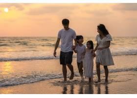 黄昏下海边沙滩嬉戏的家庭