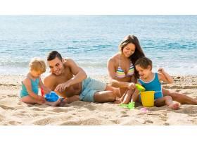 在海边玩沙子的家庭