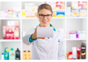 手持白色卡片展示的药房药师