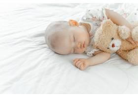 抱着小熊玩偶睡着的婴儿