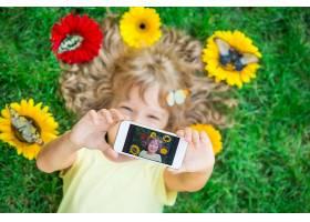 躺在草地拿手机自拍的小女孩