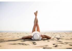 躺在沙滩上举起脚的女性