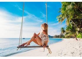 坐在海边沙滩秋千上的女性