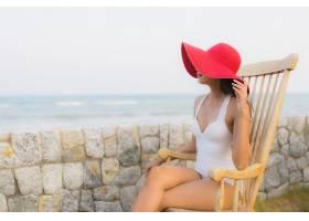坐在木椅子上看海的女性