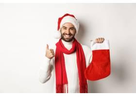 拿着红色圣诞节袜子的圣诞节派对外国男子