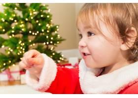 穿圣诞老人服装室内玩耍的可爱小孩
