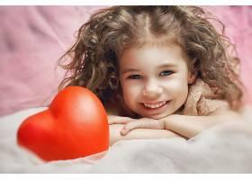 可爱微笑的小女孩与红色心形