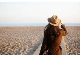 秋天沙滩上美丽的陌生女性侧观一位黑发女_943853901