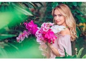 站在花园里拿着兰花的金发年轻女子_390125801