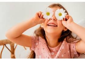 笑容满面的小女孩玩着遮住眼睛的春花_1222465401
