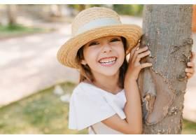笑着的浅棕色皮肤的小女孩在公园里摆姿势抚_1048513601