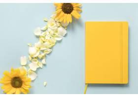 蓝色背景下向日葵和花瓣附近的黄色日记_331820901