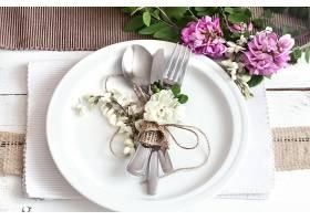 装饰精美的度假餐桌配有春天的鲜花和绿色_1010865901