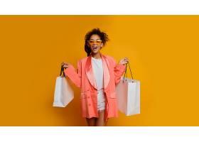 退场的黑人妇女拿着白色购物袋站在黄色背景_911612801
