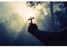 阳光明媚的少女手持十字架祈祷_395225401