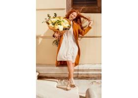 微笑的女人带着一束春天的鲜花在户外的前景_1239683201