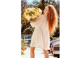 微笑的女人带着一束春天的鲜花在户外的背影_1239682801