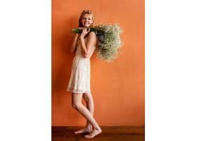 微笑的女人拿着一束鲜花摆姿势_1222471901