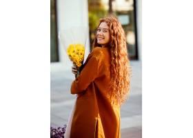 微笑的女人拿着春天的花束在户外摆姿势的侧_1239686901