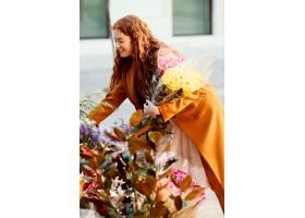 微笑的女人挑选春天的花束侧观_1239685601