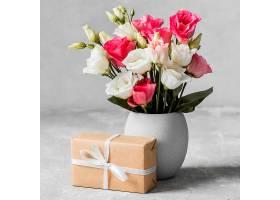 前景玫瑰花放在花瓶里旁边是包装好的礼物_1206771401