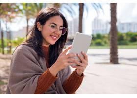微笑的美女在户外使用平板电脑_453418601