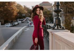 微笑着穿着紫色西装的漂亮时髦女子走在城市_1155524101