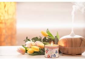 桌上芳香的油扩散灯被一束美丽的郁金香和燃_951121801