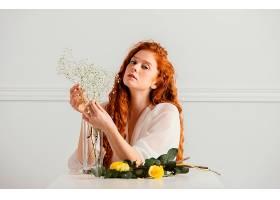 桌子上摆着春花的美女的前景_1239685801