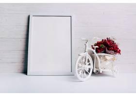 桌子上白色空白边框附近的带自行车的花瓶_383104201