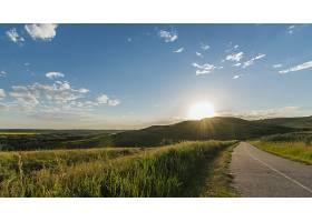在晴朗的天空下在青草和群山附近的一条道_784828301
