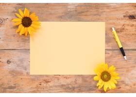 在木质背景上俯瞰带有黄色向日葵和钢笔的空_331812501