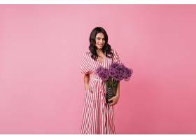 深肤色的女人自信地站在粉红色的房间里穿_1157598101